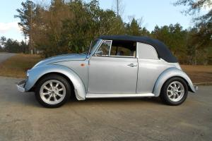1970 Volkswagen Beetle Convertible.  Bluish silver with a dark blue cloth top.